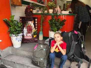 Backpakeuse attendant son bus près du petit autel des ancêtres - Saigon - Vietnam