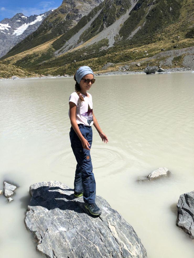 Eden joue à saute rocher dans le Hooker Lake - Mont Cook - Nouvelle Zélande